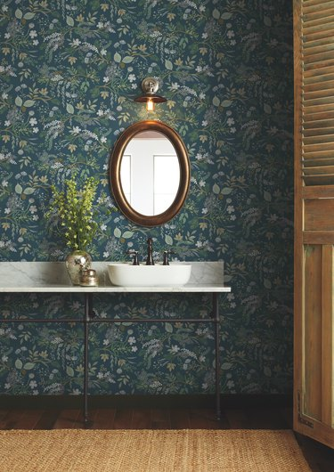 sink area with oval mirror and blue floral wallpaper
