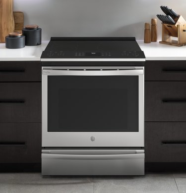 Electric range with black cabinets, white counters.