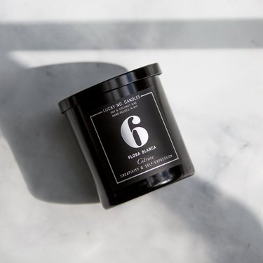 black candle with the number 6 on marble background