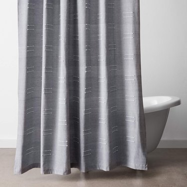 Embroidered gray eco-friendly shower curtain displayed in white bathroom