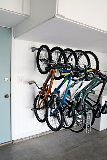bike storage rack on the wall in garage next to blue door