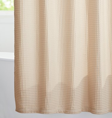 Beige waffle eco-friendly shower curtain in white bathroom with bathtub