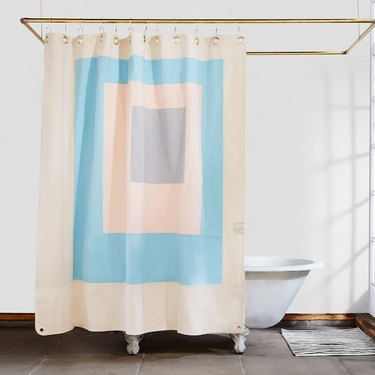 Blue and white eco-friendly shower curtain with modern design in white bathroom