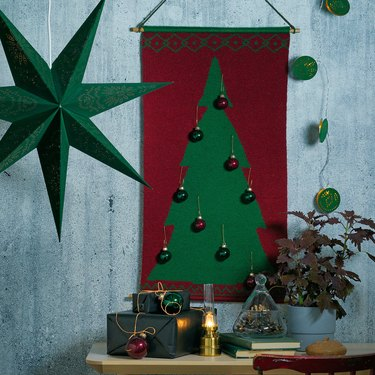 christmas set-up with red banner with green christmas tree and ornaments