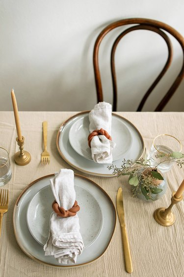 Table set with two plates and linen napkins inside DIY twisted clay napkin rings
