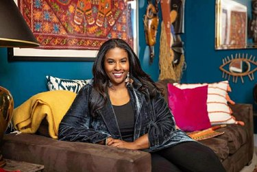 Seana Freeman on brown couch with colorful pillows and tribal wall hangings