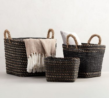 Handwoven black storage containers holding a pillow and throw blanket