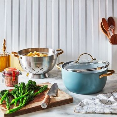 ceramic cookware in a kitchen next to a cutting board with broccoli and a knife
