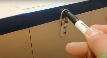 person marking hanging hardware on blue piece of masking tape