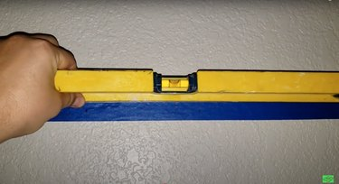 blue masking tape with blue markings on wall with level