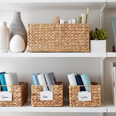 Water hyacinth storage containers on white shelves with books