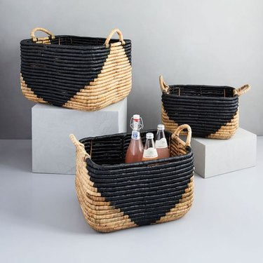 Black geometric storage containers in seagrass with handles