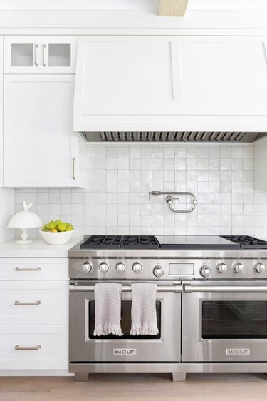 stainless steel double oven and gas stovetop in white kitchen