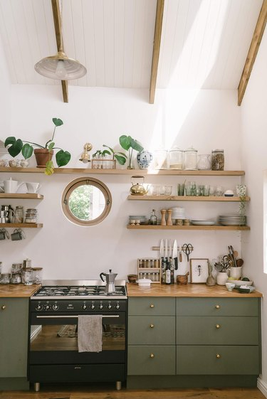 white and sage green kitchen with gas stovetop
