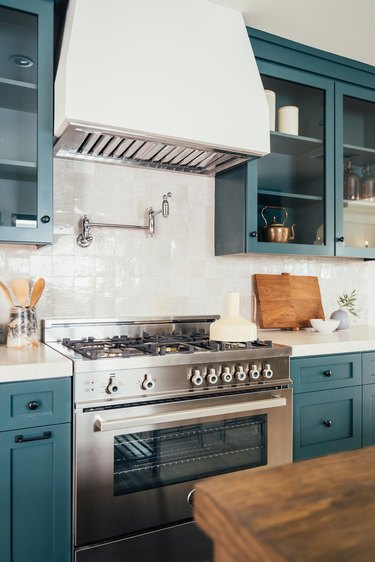 stainless steel gas stovetop with blue cabinets