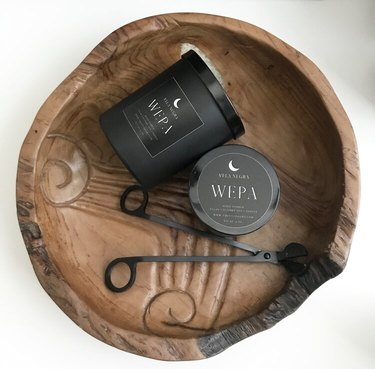 black candles and wick trimmer in wood bowl
