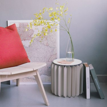 Circular folded paper table with vase on top and books leaning against it