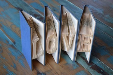 """Book sculpture of four books with blue covers and folded paper spelling """"Love"""""""