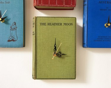 Four wall clocks with book-cover faces in different colors