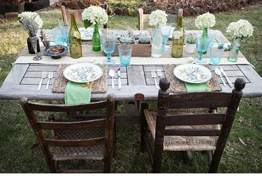 Vintage barn door repurposed as dining table with two wood chairs and table set with flowers and glassware