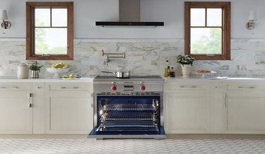 stove brand Wolf in a white kitchen with two windows and white countertops with wolf stove in the center