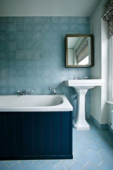 Pedestal Sink Storage Ideas in Bathroom with white pedestal sink, blue tile on walls and floors, medicine cabinet, navy blue wood siding on bathtub.