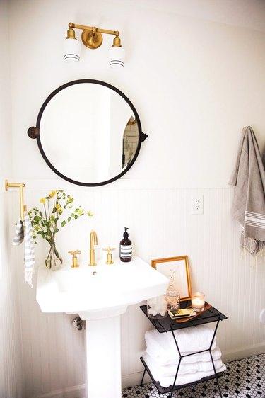 Pedestal Sink Storage Ideas in Bathroom with white pedestal sink, round mirror, sconce light, black side table