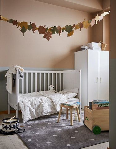 nursery with gray and white dotted rug and hanging decor