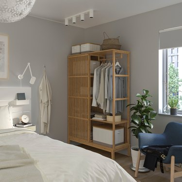bedroom with white sheets and wardrobe