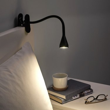 bedside with clipped lamp and books