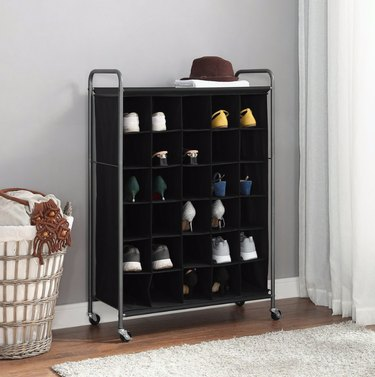 Black shoe organizer on wheels, neutral rug, laundry basket.