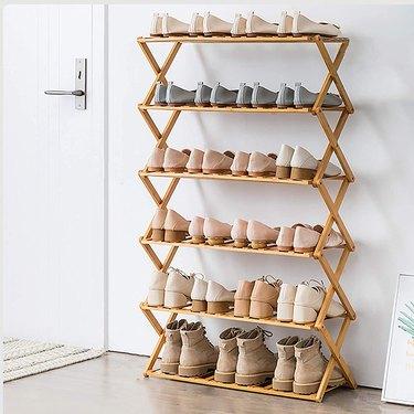 Wood folding shoe organizer by front door.