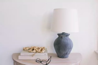 Chalkboard spray painted lamp on table with books and glasses