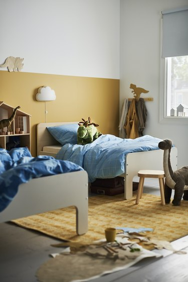 kids bedroom with yellow colorblock wall and yellow rug