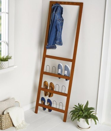 Wood shoe organizer and coat rack, plant in white pot, blankets in basket.