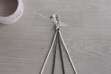 Four strands of cord tied into a knot and taped down to table