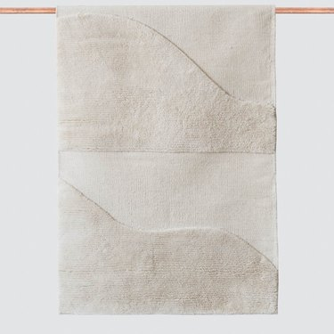 White eco-friendly rug with curved design hanging on copper rod