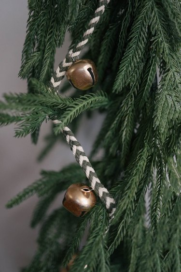 DIY jingle bell garland strung in a Christmas tree