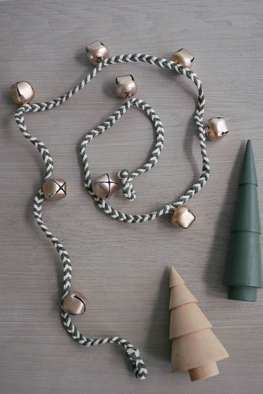 DIY jingle bell garland next to two wooden holiday trees