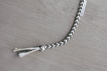 Four strands of macrame cord braided into fishtail braid