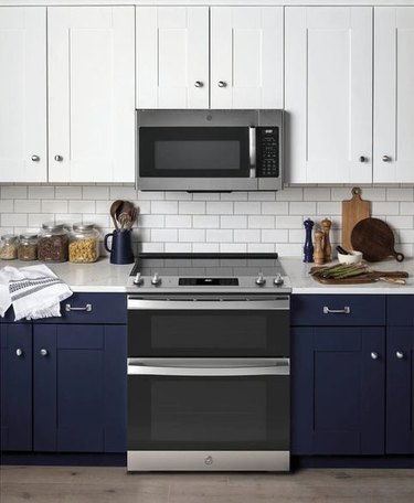 stove brand GE in a blue and white kitchen with stove and microwave