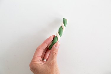 Wrapping a piece of green clay with white clay