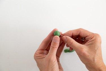 Sticking a needle through a ball of green clay