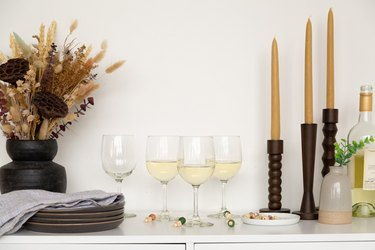 Wine classes on counter with candles and black vase with dried flowers