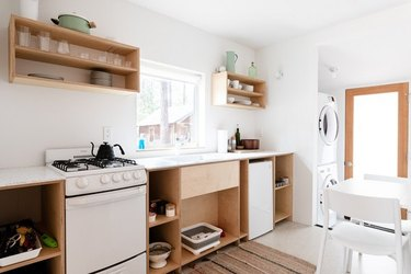 Kitchen with small stove, plywood shelves, small fridge, white table and chairs. stove size