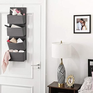 Over the Door Storage with Gray storage bins hanging on door, lamp, photos, nightstand.