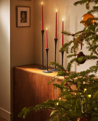 side table with red candles in black holders and christmas tree nearby
