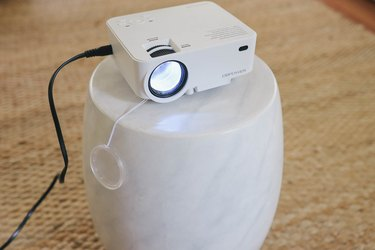 Mini projector machine set on small side table