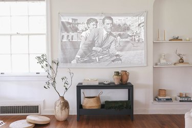 DIY portable projector screen hanging on wall in living room above console table