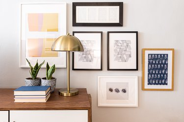 gallery wall and console table with brass lamp